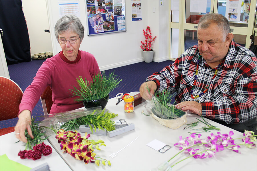 Elderly woman and man working on their flowers